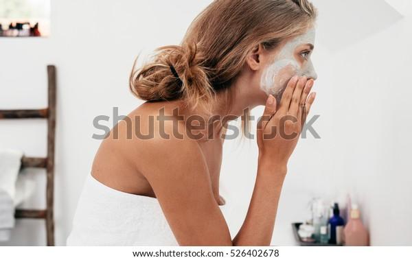 浴室で美容マスクを塗る若い女性のサイドビューショット。 顔の皮を大事にする女性。