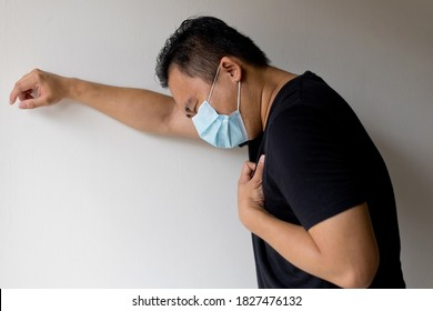 Side View Of An Sick Asian Man In A Medical Disposable Mask, Feeling Difficulty Breathing, Standing Against Wall