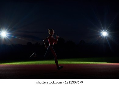 Side view of silhouette of woman running forward in darkness on stadium only with two lights from two sides. Sports girl training at night alone, doing big steps to competition. Concept of sport.