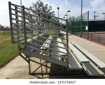 Side view of silver bleachers with five seats.