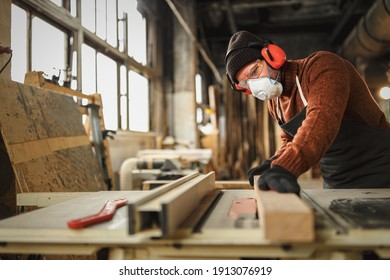 Side view of skilled carpenter in protective respirator and headphones cutting lumber plank on workbench in professional workshop