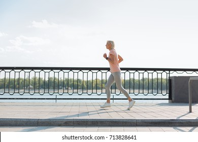 Side view of slender senior woman jogging on bridge