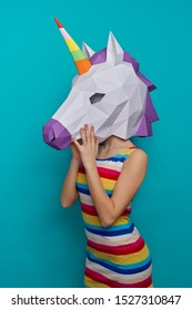 Side view of slim female in colorful dress wearing 3d paper craft in form of unicorn on blue isolated background. Positive childish girl posing in studio. Concept of happiness and childhood.