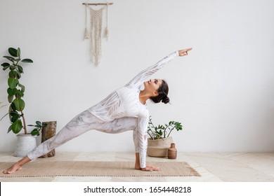 Seitenansicht der schlanken, ziemlich positiven jungen Brunette Frau, die Utthita parsvakonasana Bewegung, Extended Side Angle Pose, auf Matte auf dem Boden, umgeben von Hauspflanzen auf weißer Wand. Yoga und Pilze