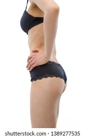 side view . slim young sports girl in black underwear shows her figure, sporty buttocks. isolated on a light background. without retouching..
