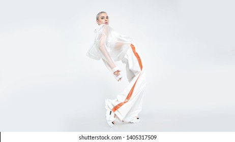 Side view of slim young woman with short hair and in trendy futuristic clothes bending back and looking away while performing dance movement against white background