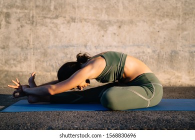 Side view of slim young woman in sport clothes on fitness mat arranged on asphalt making forward bend yoga pose on street at sunny day