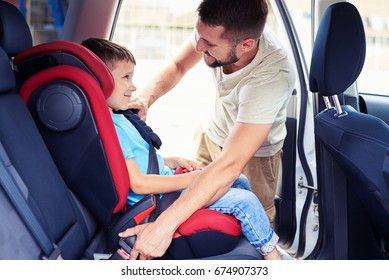 Side view of small handsome son in car seat being put in back of car by father