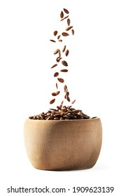 Side view of small wooden bowl filling with linseed or flax seed falling down and isolated on white background