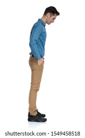 side view of smart casual man waiting in line and looking down, standing isolated on white background, full body