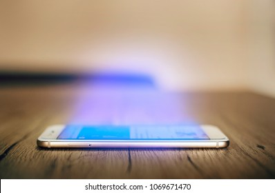 Side view of Smartphone on the wooden table with hypnotic blue light glowing from the screen. Protective glass cover. Addicted to smartphone concept. Selective focus on phone, low depth of field.