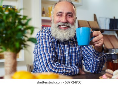 Side view of smiley senior man. Holding a cup of tea in hands. Sitting in the kitchen in the morning. Man wearing a checked shirt posing at the camera at home