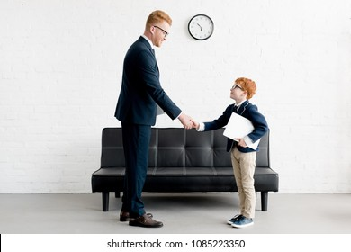 side view of smiling adult and preteen businessmen shaking hands in office