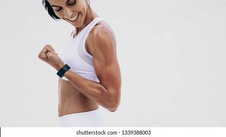 Side view of a smiling athletic woman looking at her biceps during fitness training. Cheerful fitness woman doing fitness training.