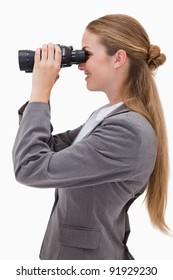 Side view of smiling bank employee with spyglasses against a white background