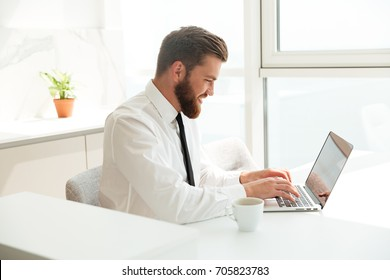 Side view of a smiling bearded business man using laptop computer by the table in kitchen