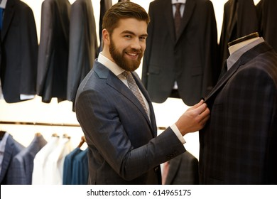 Side view of smiling bearded man in suit choosing a jacket in shop while looking at camera
