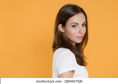 Side view of smiling beautiful attractive young brunette woman 20s in white blank empty design casual t-shirt posing standing looking camera isolated on yellow color wall background studio portrait