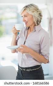 Side view of a smiling beautiful businesswoman drinking tea in the bright office
