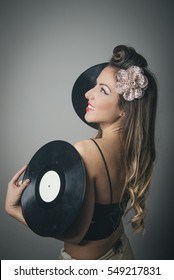 Side view of smiling beautiful young woman with two vinyl records, studio background
