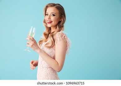 Side view of Smiling blonde woman in dress drinking champange and looking at the camera over turquoise background