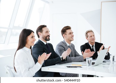 Side view of Smiling Business people sitting by the table and applauded in conference room