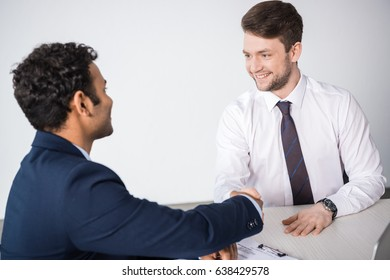 side view of smiling businessmen shaking hands at workplace