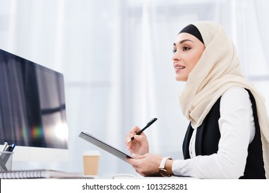side view of smiling businesswoman in hijab with documents at workplace in office