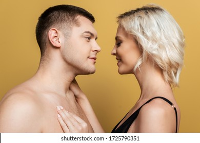 side view of smiling couple looking at each other on yellow background