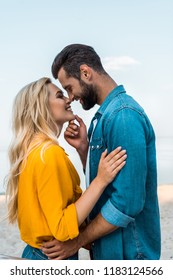 side view of smiling couple touching with noses on beach