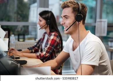 Side view of Smiling Coworkers sit by the table in headphones. Call center