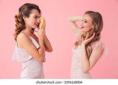 Side view of Smiling elegant brunette woman making photo on hipster camera her pretty blonde woman in dress over pink background