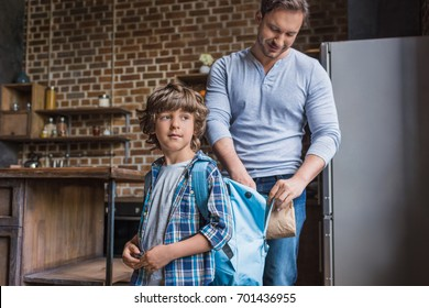side view of smiling father putting school lunch into sons backpack