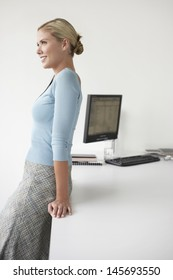 Side view of a smiling female executive leaning on desk in office