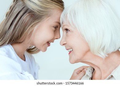 side view of smiling granddaughter and grandmother looking at each other isolated on grey