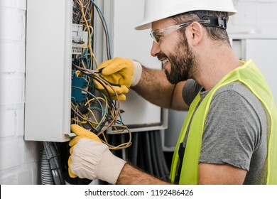 side view of smiling handsome electrician repairing electrical box with pliers in corridor