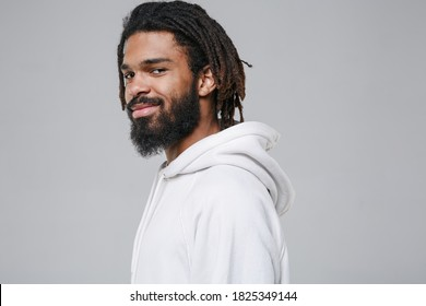 Side view of smiling handsome young african american man with dreadlocks 20s wearing white casual streetwear hoodie posing looking camera isolated on grey color wall background studio portrait