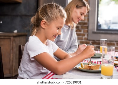 side view of smiling little girl having lunch together with mother