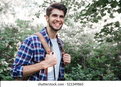 Side view of smiling man with backpack in forest. holds on to the harness. man in shirt.
