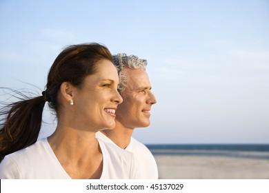 Seitenansicht eines lachenden Paares mittleren Alters am Strand, der zusammen in die Ferne schaut. Horizontaler Schuss.