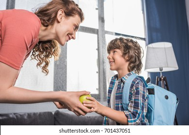 side view of smiling mother giving fresh apple to son before school