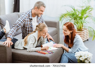 side view of smiling parents helping teenage daughter with homework at home