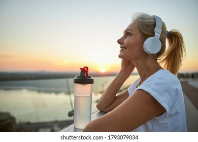 Side view of a smiling pleased modern middle-aged female in headphones enjoying her favorite songs