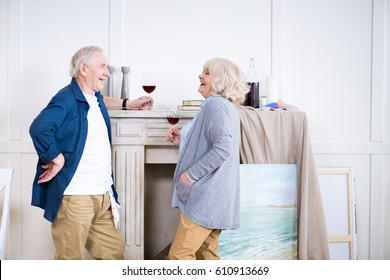 side view of smiling senior couple drinking wine in art workshop