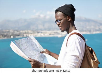 Side view of smiling trendy looking young dark-skinned hitchhiker studying paper map in his hands, planning route and stops during vacations abroad, vast azure sea and resort town in background