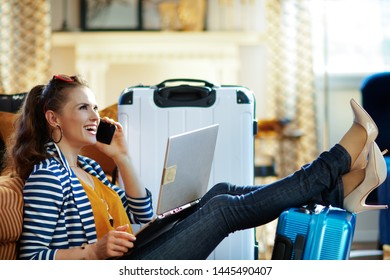 Side view of smiling trendy woman in striped jacket sitting near couch and trolley bags in the modern living room in sunny hot summer day booking trip online on a laptop and using ai call center.