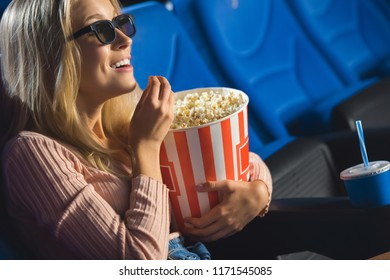 side view of smiling woman in 3d glasses with popcorn watching film alone in cinema