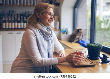 Side view of smiling woman enjoying cup of tea in cafe