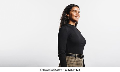 Side view of smiling woman standing against white background. Portrait of cheerful young woman looking away.