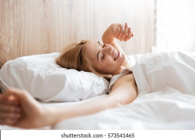 Side view of smiling woman waking up after sleep on bed